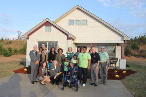 The Dixon family and UAB employees, staff and volunteers in front of the Dixon's new home. Photo by Chris Yow