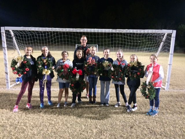 Youth soccer players spread holiday cheer to elderly