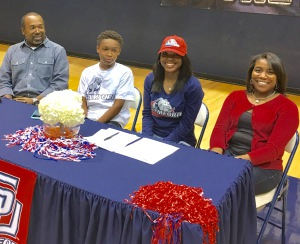Raven Omar, second from right, signs with Samford as her family looks on.
